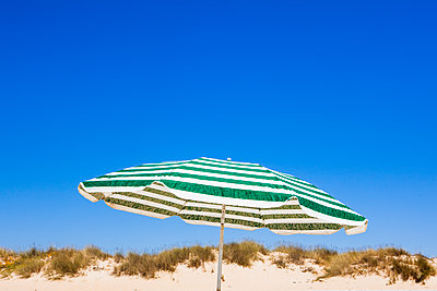 A beach umbrella offering shelter to holiday makers while on a sandy beach in the hot sun of a Spanish summer. - p1057m2164312 by Stephen Shepherd