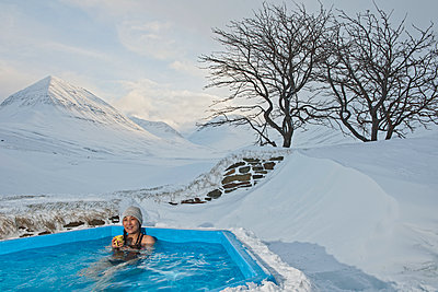 Woman enjoying hot tub at ski lodge in Iceland - p1166m2268879 by Cavan Images