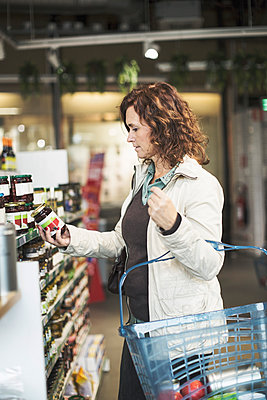 Side view of woman reading label on bottle while shopping in supermarket - p426m1407393 by Kentaroo Tryman