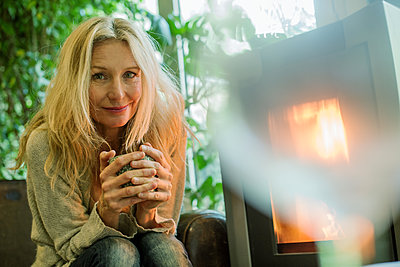 Mature woman relaxing by fireplace with warm drink, portrait - p623m1571037 by Frederic Cirou