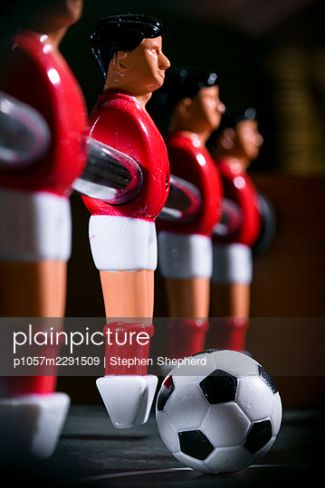Detail of a table football game showing the plastic players or figures lined up on their bar with an outsize football on the hard green playing surface. - p1057m2291509 by Stephen Shepherd