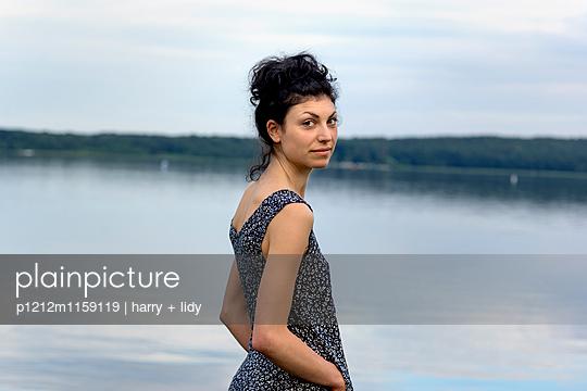 Portrait einer jungen Frau am Ufer - p1212m1159119 von harry + lidy
