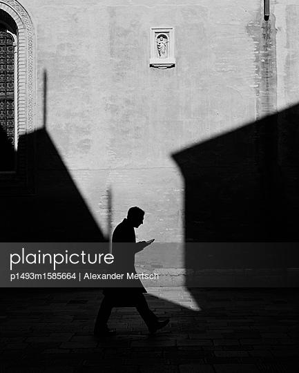 Mann mit Buch im Schatten vor Kirche, Venedig, schwarzweiß - p1493m1585664 von Alexander Mertsch