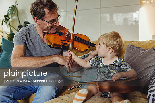 Toddler watching his father playing violin - p300m2140614 by Mareen Fischinger