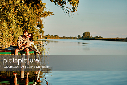 Couple reflected in water sitting on jetty at a lake - p300m2207103 by Zeljko Dangubic