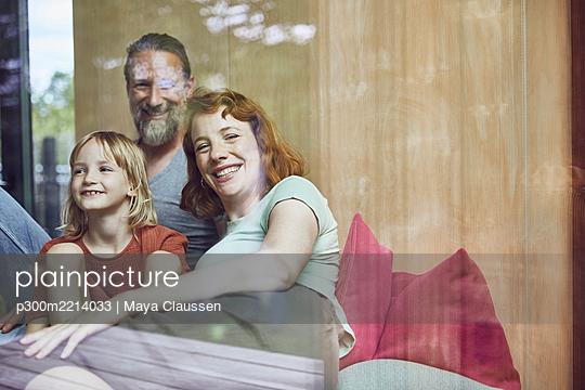 Smiling parents with daughter relaxing on bed at home seen through window - p300m2214033 by Maya Claussen