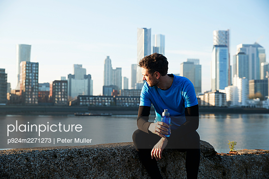 UK, London, Jogger looking at downtown skyline in background - p924m2271273 by Peter Muller