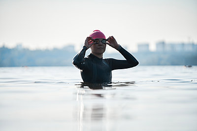 Woman swimmer in pink rubber hat puts on glasses while standing in background of water - p1630m2203529 by Sergey Mironov