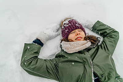 Girl in green jacket with eyes closed making snow angle during vacations - p300m2256350 by Oxana Guryanova