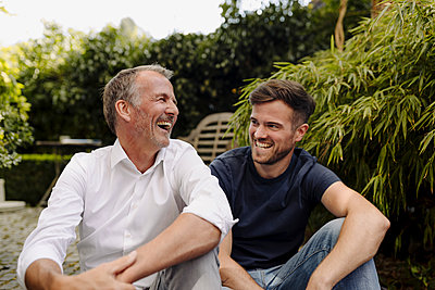 Father and son laughing while sitting together in backyard - p300m2276927 by Gustafsson