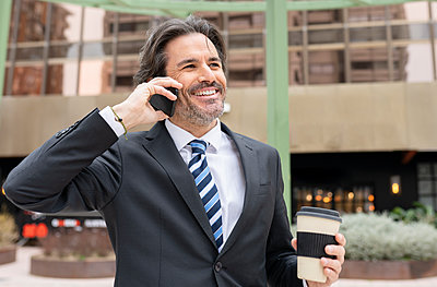 Smiling businessman with coffee cup talking on mobile phone in office park - p300m2277177 by Jose Carlos Ichiro