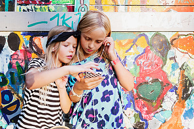 Girls listening music through mobile phone while standing against graffiti wall - p426m1226377 by Maskot