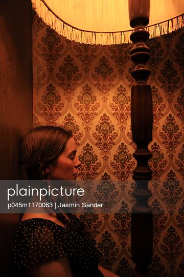 Frau sitzt unter Lampenschirm - p045m1170063 von Jasmin Sander