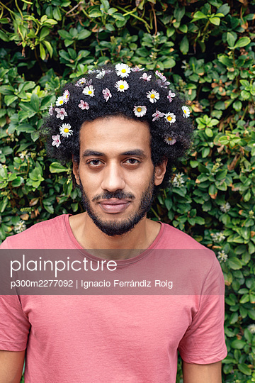 Afro young man with flowers in hair standing in front of plants - p300m2277092 by Ignacio Ferrándiz Roig