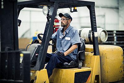 Serious manual worker sitting in forklift at metal industry - p1166m1526543 by Cavan Images