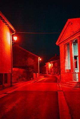 Street lamps light up a narrow village street - p1681m2263275 by Juan Alfonso Solis