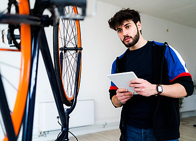 Man looking at upturnt bicycle while holding digital tablet at home - p300m2274527 by Giorgio Fochesato