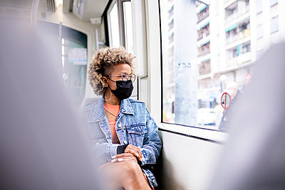 Woman wearing protective face mask looking through tram window - p300m2276415 by Rafael Fernandez Torres