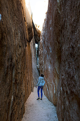 Woman standing in crevasse in Joshua Tree National Park, California, USA - p343m1500364 by Natasha Shapiro