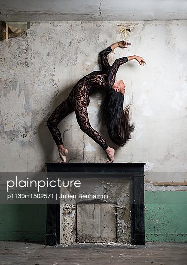 Female dancer with long black hair on mantelpiece - p1139m1502571 by Julien Benhamou