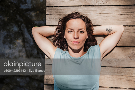Mid adult woman with hands behind head lying on pier by lake in forest - p300m2293443 by Eva Blanco