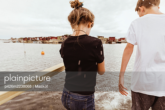 Rear view of siblings playing in water during vacation - p426m2238068 by Maskot