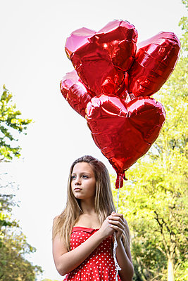 Female teenager holding heart-shaped balloons - p1019m1496310 by Stephen Carroll