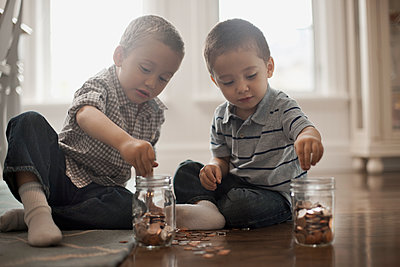 Two children playing with coins, dropping them into glass jars. - p1100m1095646 by Mint Images