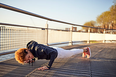 Side view of determined young woman doing push-ups on metallic footpath - p1166m1474172 by Cavan Images
