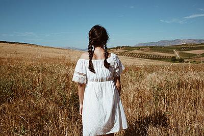 Rear view of brunette girl in rural landscape - p1623m2289591 by Donatella Loi