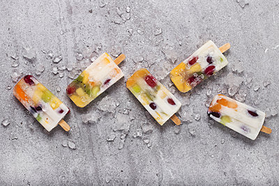 Homemade fruits and yogurt ice lollies on marble - p300m1581739 von Retales Botijero