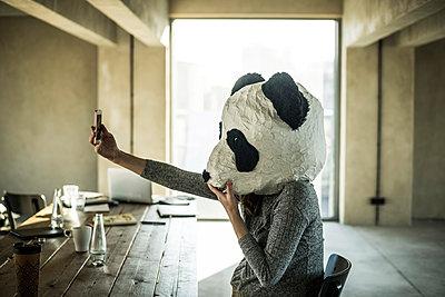 Woman with panda mask sitting in office, taking selfie - p300m2104276 von Malte Jäger