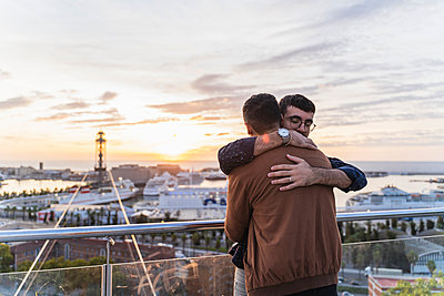 Gay couple hugging on lookout above the city with view to the port, Barcelona, Spain - p300m2154490 by VITTA GALLERY
