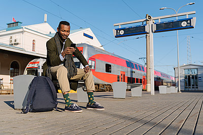 Stylish man using smartphone while waiting for the train - p300m2155330 by Hernandez and Sorokina