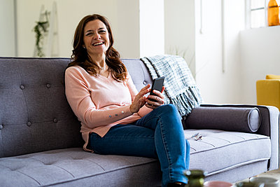 Happy mature woman holding mobile phone while sitting on sofa in living room - p300m2265319 by Giorgio Fochesato