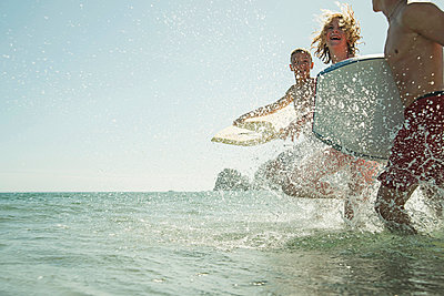 Three teenagers with surfboards running at waterside of the sea - p300m965383f by Uwe Umstätter