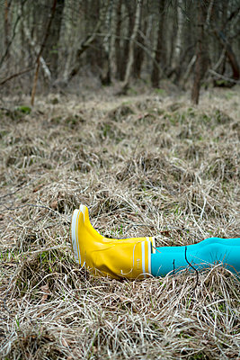 Woman in yellow rubber boots lies on forest soil - p427m1333074 by Ralf Mohr