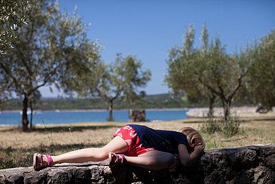 Mädchen schläft auf einer Steinmauer - p906m1362783 von Wassily Zittel