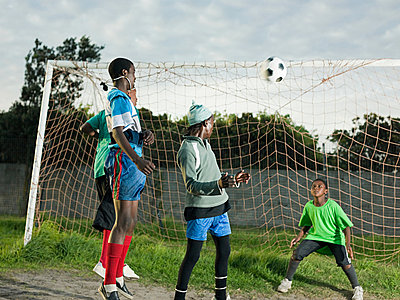 Teenage boys playing football - p9246602f by Image Source