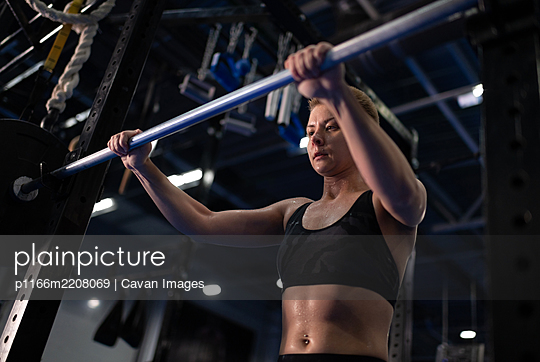 Exhausted female athlete taking barbell from rack - p1166m2208069 by Cavan Images