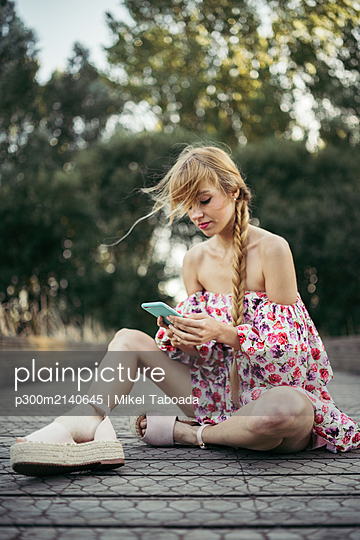 Portrait of young woman wearing summer dress with floral design sitting on boardwalk using cell phone - p300m2140645 by Mikel Taboada