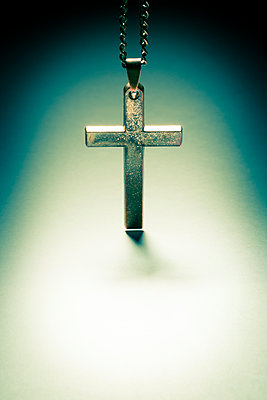 An old metal cross or crucifix hanging from a metal chain, a religious icon or symbol often used by the christian faith. - p1057m1572922 by Stephen Shepherd