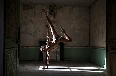 Bare-chested dancer doing a handstand - p1139m1503039 by Julien Benhamou