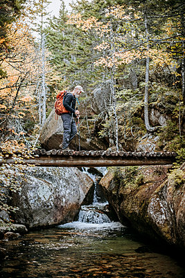 An older hiker crosses a bridge over a stream while walking in Maine - p1166m2106823 by Cavan Images