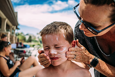 mother putting sun screen on son's face - p1166m2182784 by Cavan Images