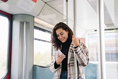 Smiling young woman using smartphone on a subway - p300m2143398 von Hernandez and Sorokina