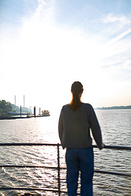Young woman looks out over the Elbe river - p341m2210410 by Mikesch