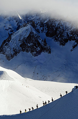 Europe, France, French Alps, Haute Savoie, Chamonix, Aiguille du Midi, skiers walking down the ridge at the start of Vallee Blanche off piste - p652m716731 by Christian Kober
