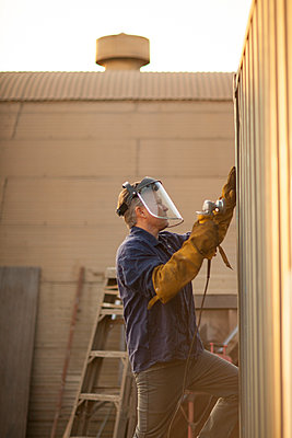 Welder using power tool on shipping container - p924m1422749 by Raphye Alexius