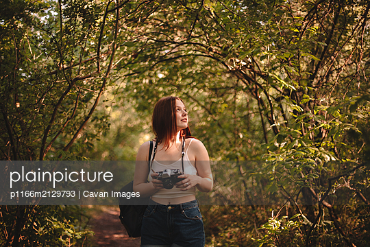 Female tourist holding camera while standing in forest during summer - p1166m2129793 by Cavan Images